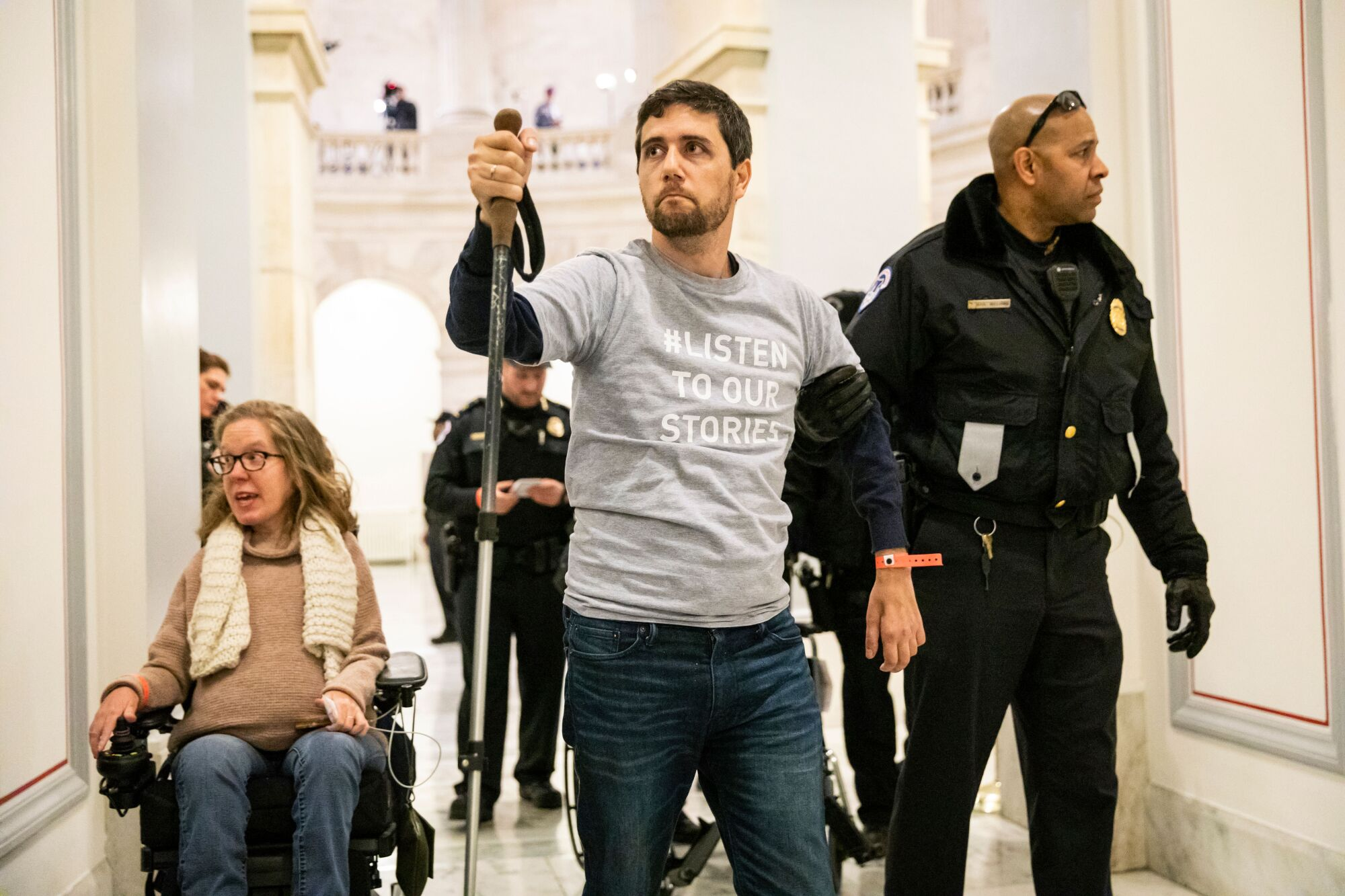 A woman in a wheelchair, a man walking with a hiking pole and several security officers.