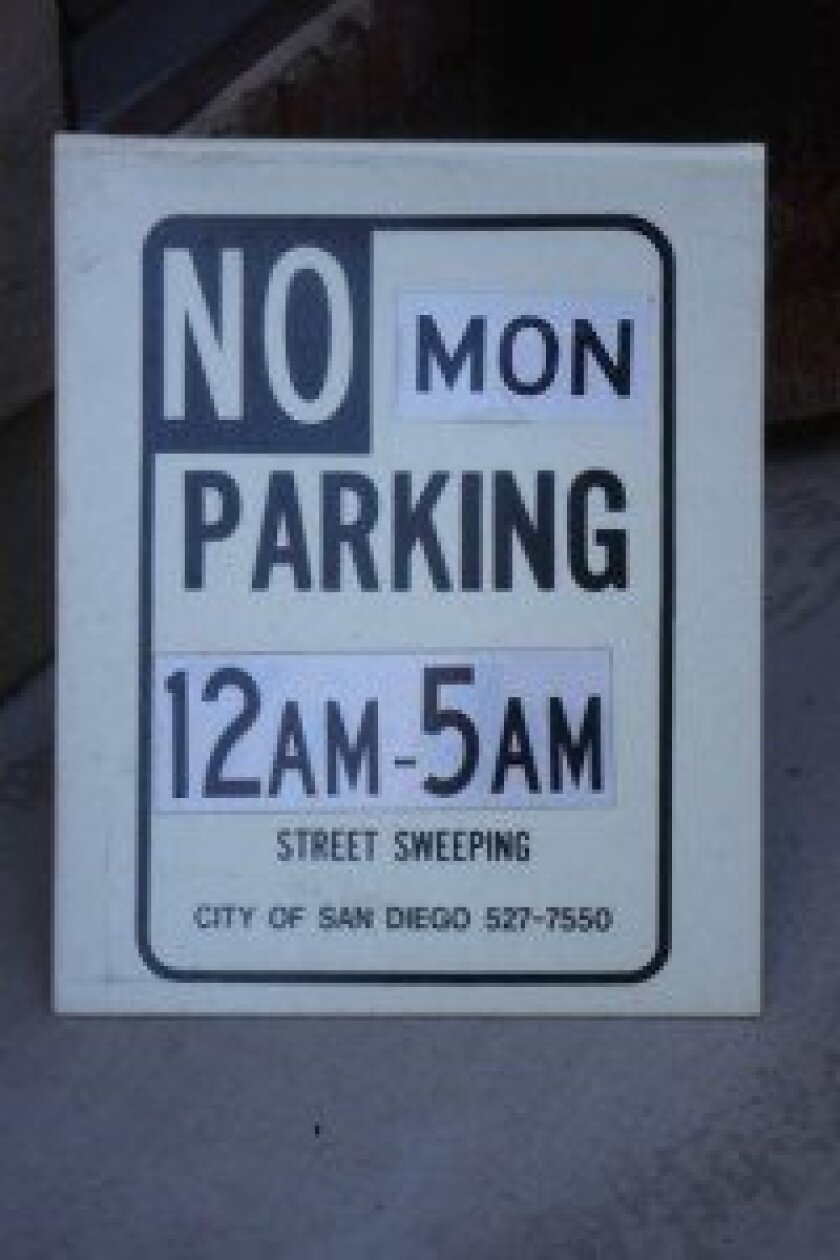 La Jolla resident Edward Nigolian posts these signs on his street hoping neighbors will move their cars to ensure thorough street sweeping. Ashley Mackin