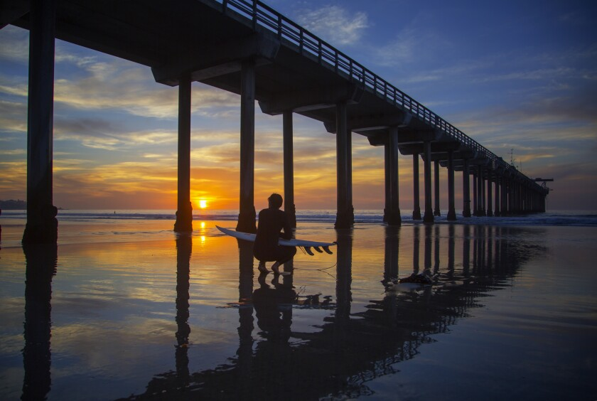 A surfer looks for an entry point from Scripps Pier during sunset.