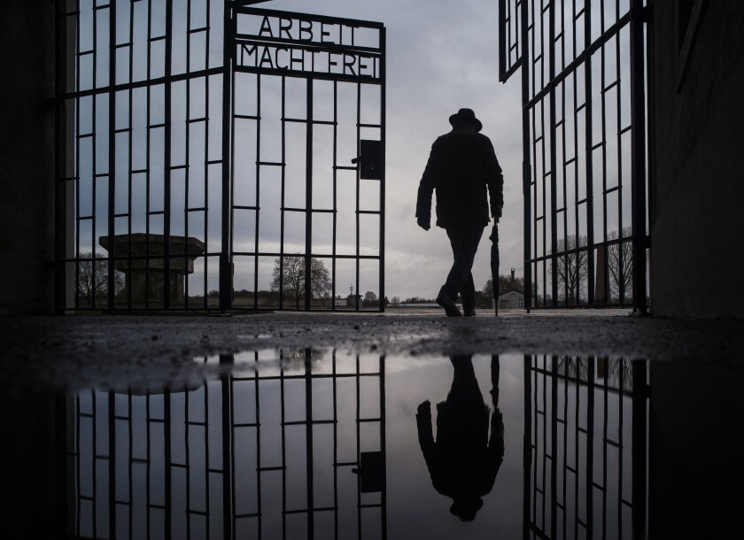 File - In this Sunday, Jan. 27, 2019 file photo, a man walks through the gate of the Sachsenhausen Nazi death camp with the phrase 'Arbeit macht frei' (work sets you free) during International Holocaust Remembrance Day in Oranienburg, about 30 kilometers (18 miles), north of Berlin, Germany. Hundreds of Holocaust survivors in Austria and Slovakia are getting vaccinated against the coronavirus exactly 76 years after the liberation of the Nazi's Auschwitz death camp. More than 400 Austrian survivors were invited to get the vaccine at Vienna's biggest mass vaccination center on International Holocaust Remembrance Day on Wednesday Jan. 27, 2021. (AP Photo/Markus Schreiber, file)