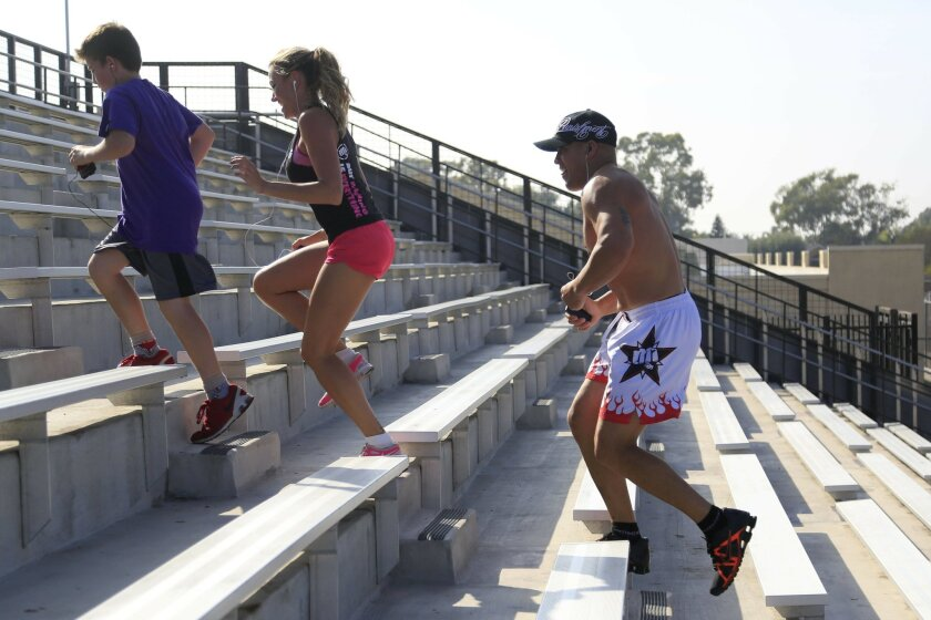 October 11th, 2014 Huntington Beach, CA- Mixed martial arts fighter Tito Ortiz runs with his girlfriend Amber Nichole Miller and his oldest son during a fifteen minute cardio workout at his former high school, Huntington Beach High School. Photo by David Brooks/ U-T San Diego MANDATORY PHOTO CREDIT DAVID BROOKS / U-T SAN DIEGO; ZUMA Press.