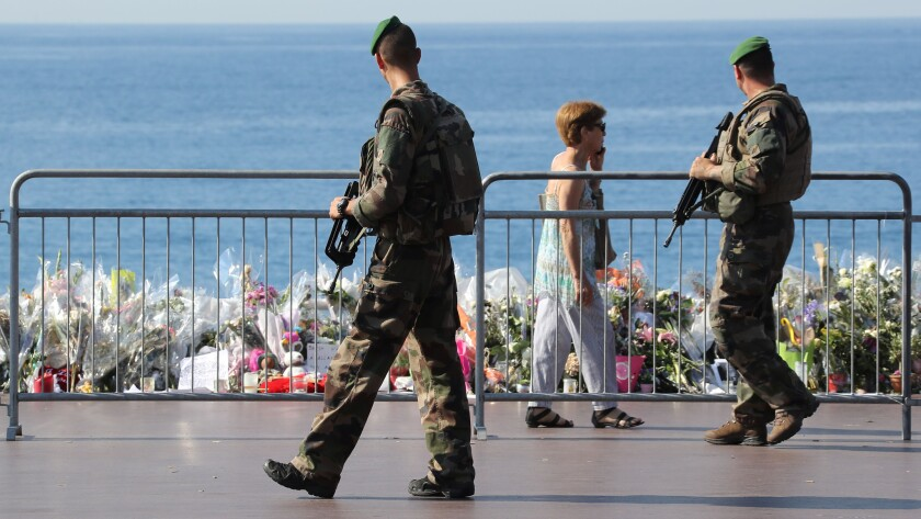 Soldiers on Tuesday pass by the new makeshift memorial for the victims of the Bastille Day attack in Nice, France. The flowers on the Promenade des Anglais were moved closer to the seafront so that the road could be reopened.