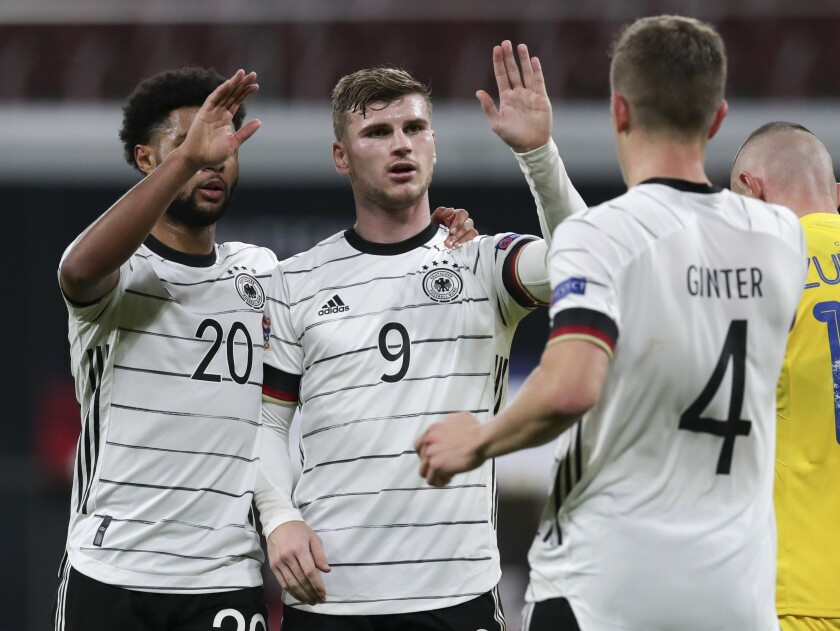 Germany's Timo Werner, centre, celebrates with teammates Serge Gnabry, left, and Matthias Ginter, right, after scoring his team's third goal during the UEFA Nations League soccer match between Germany and the Ukraine at the Red Bull Arena in Leipzig, Germany, Saturday, Nov. 14, 2020. (AP Photo/Michael Sohn)