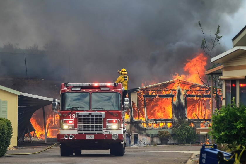 Firefighters wait for water as they battle flames at the Alpine Oaks Estates mobile home park on Friday during a fire in Alpine, California.