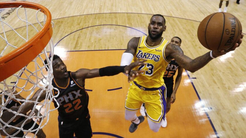 Los Angeles Lakers forward LeBron James (23) drives past Phoenix Suns center Deandre Ayton during th