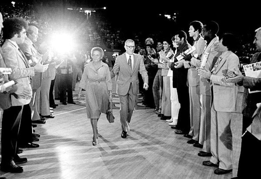 John and Nell Wooden pass between former UCLA players who are honoring Wooden on his 65th birthday on Oct. 14, 1975, at Pauley Pavilion.