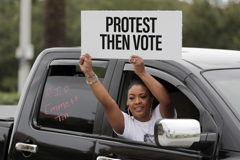 """A woman holds a sign saying """"Protest Then Vote"""" during a mock funeral procession in Hallandale Beach, Fla."""
