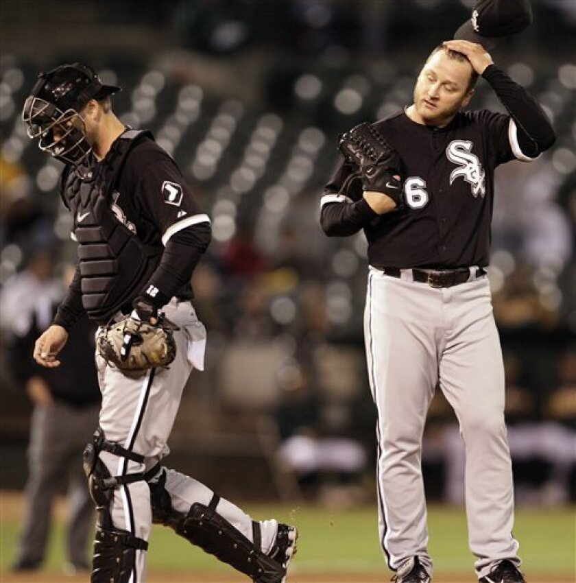 Chicago White Sox's Mark Buehrle, right, removes his cap after a conversation on the mound with catcher A.J. Pierzynski during the fifth inning of a baseball game against the Oakland Athletics Tuesday, Sept. 21, 2010, in Oakland, Calif. (AP Photo/Ben Margot)