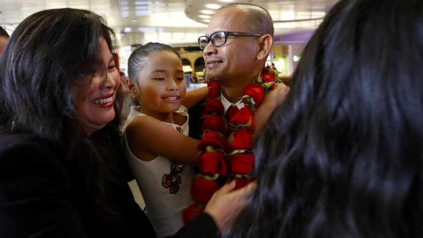 Meach Sovannara, center, at LAX on Saturday greets family including his wife, Jamie Meach, left, and youngest daughter, Sarai Sovannara, 10.