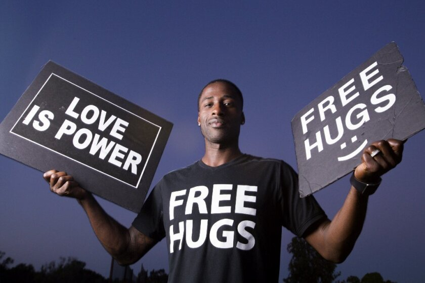 """Ken E. Nwadike Jr., known as the """"Free Hugs Guy,"""" poses outside his Bonita office with signs he carries around the nation to events where he surprises people with hugs."""