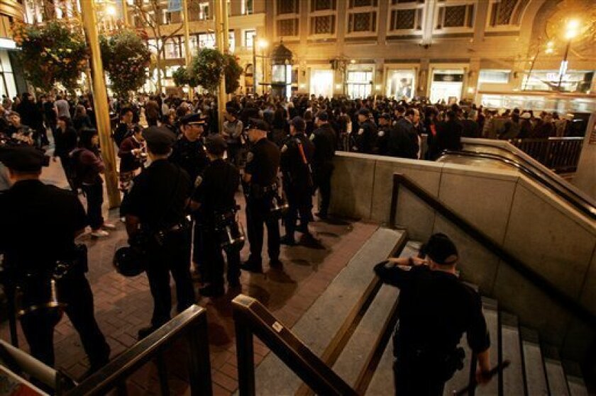 Police keep watch in front of a BART train station entrance during a protest against the shooting death of Oscar Grant, in San Francisco, Monday, Jan. 12, 2009. Grant was shot and killed by a BART police officer after an altercation on a train station platform in Oakland on New Year's Day.  (AP Pho