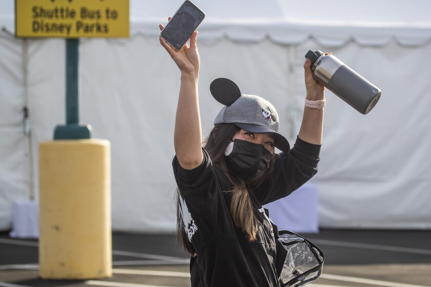 Anaheim, CA - January 13: An Orange County active Phase 1A (critical and healthcare workers) resident wearing Micky Mouse ears hat celebrates as she exits large tents at Orange County's first large-scale vaccination site after receiving the Moderna COVID-19 vaccine in the Toy Story parking lot at the Disneyland Resort in Anaheim Wednesday, Jan. 13, 2021. Orange County supervisors and Orange County Health Care Agency Director Dr. Clayton Chau held a news conference discussing the county's first Super POD (point-of-dispensing) site for COVID-19 vaccine distribution. The vaccinations are at Tier 1A for people who have reservations on a website. The site is able to handle 7,000 immunizations per day. Their goal is to immunize everyone in Orange County who chooses to do so by July 4th. (Allen J. Schaben / Los Angeles Times)
