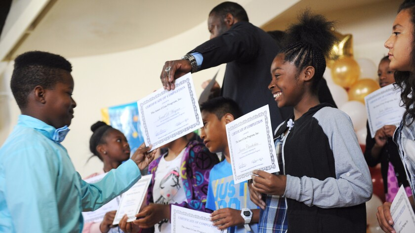 Students attend a graduation ceremony at Century Academy for Excellence Charter School in Inglewood on May 23.