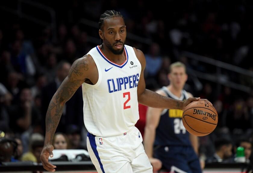 Clippers star Kawhi Leonard controls the ball against the Denver Nuggets.