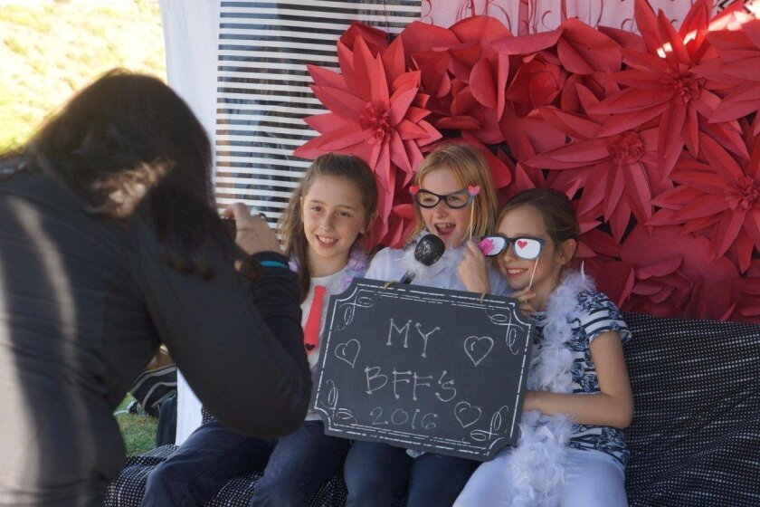 """Encinitas Country Day Schools students recently enjoyed a Valentine's Day festival to raise money for the Clearity Foundation. Elara Kerwin, Miri Hughes and Rhea Kerwin have their photos taken as """"BFFs"""" (best friends forever) at the festival by Susan Bachand, event co-chairwoman."""