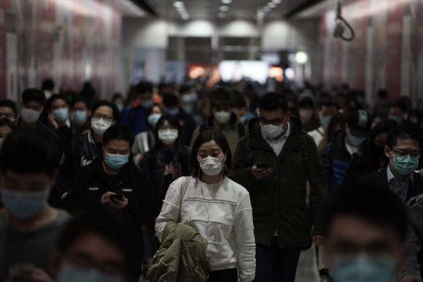 People wearing masks, walk in a subway station, in Hong Kong, Friday, Feb. 7, 2020. Hong Kong on Friday confirmed 25 cases of a new virus that originated in the Chinese province of Hubei. According to the latest figures, 233 new cases of the novel coronavirus have been confirmed globally, Hong Kong's Chief Secretary for Admissions told a news conference. (AP Photo/Kin Cheung)