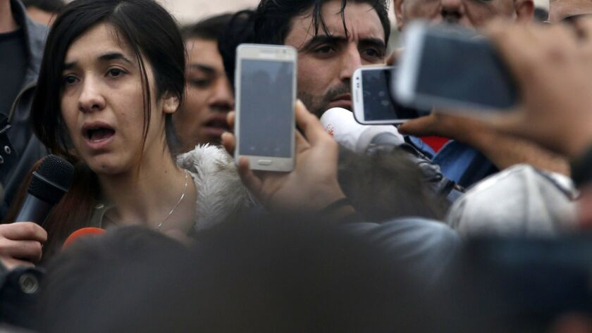 Nadia Murad, left, speaks during her 2016 visit in a makeshift refugee camp at the northern Greek border point of Idomeni, Greece. On Friday, the activist was awarded the Nobel Peace Prize.