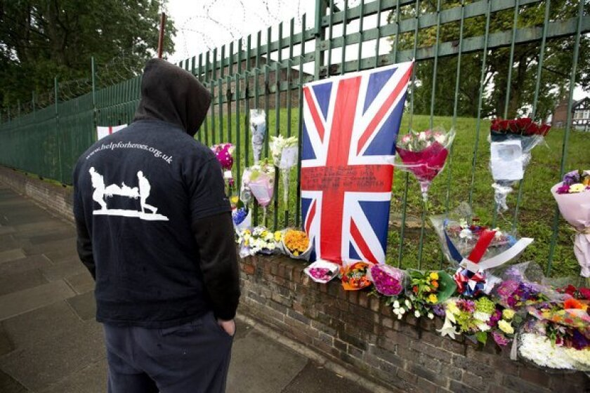 A man wearing a Help the Heroes jacket pauses at the makeshift memorial erected at the site where soldier Lee Rigby was killed outside Woolwich Barracks in London. Help the Heroes is a British charity for wounded soldiers.