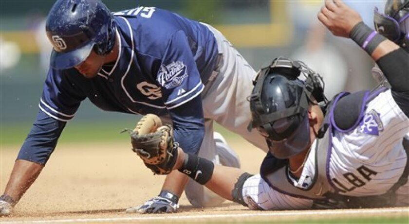 Colorado Rockies catcher Yorvit Torrealba, right, tags out San Diego Padres' Jesus Guzman, after tagging out Jedd Gyorko for an unassisted double play during the sixth inning of a baseball game Wednesday, Aug. 14, 2013 in Denver. (AP Photo/Barry Gutierrez)