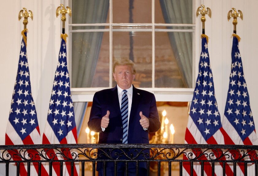 President Trump gives a thumbs up Monday at the White House after he was hospitalized for three days for COVID-19.