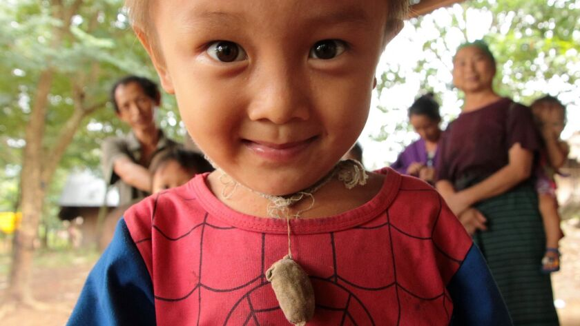 A Hmong boy, wearing an amulet, instigated a fun screech-filled game of chase with me in his village