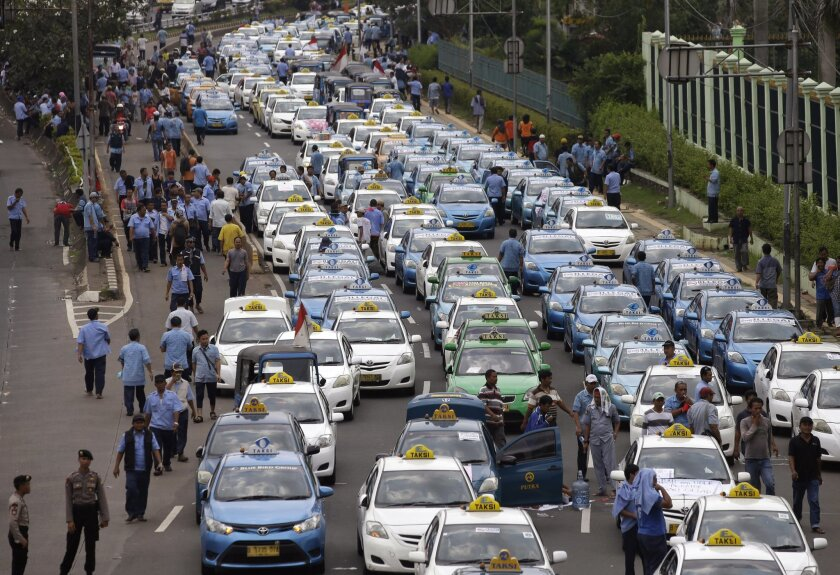 Taxis are lined up during a protest against competition from ride-hailing apps such as Uber and Grab at the main business district in Jakarta, Indonesia, Tuesday, March 22, 2016. (AP Photo/Achmad Ibrahim)