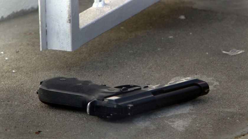 A gun lies on the ground as Los Angeles Police investigate the scene of a shooting.