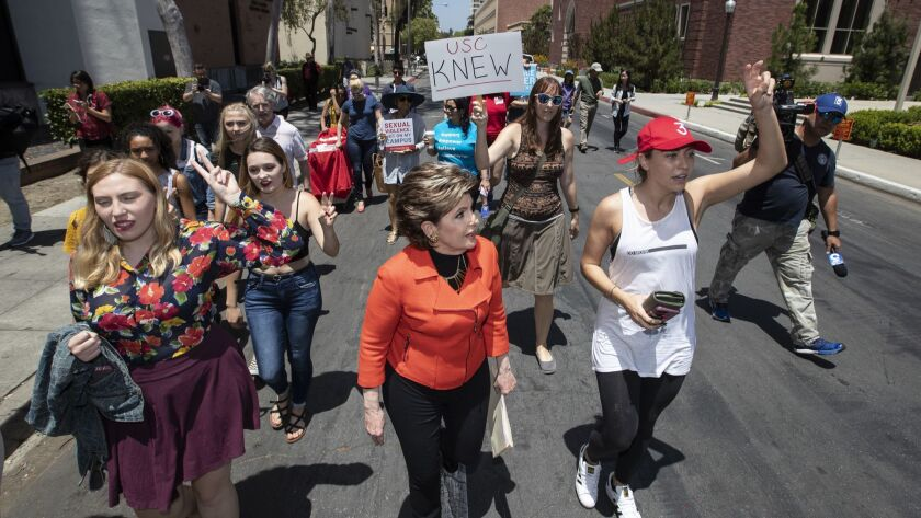 Attorney Gloria Allred, center, joins a march Saturday at USC to protest officials' handling of sexual misconduct allegations involving a former university gynecologist.