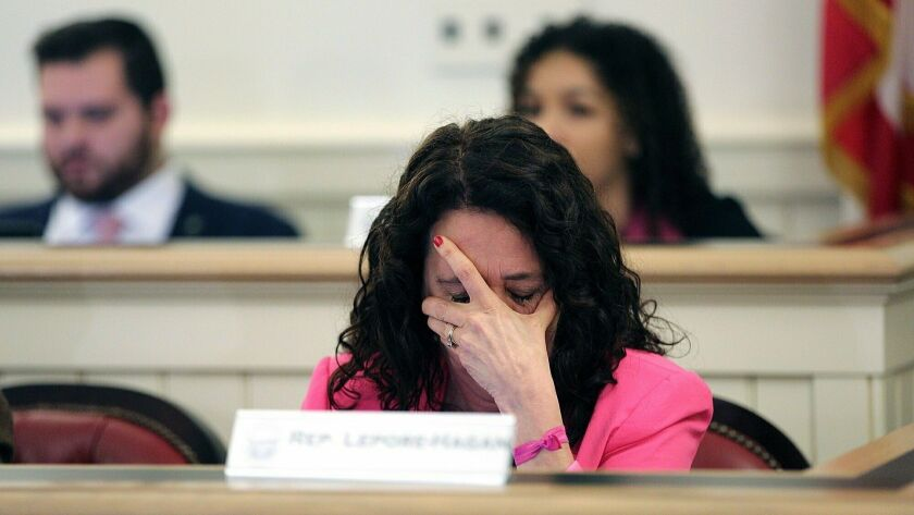 Ohio Representative Michele Lepore-Hagan wipes tears from her face during a hearing to propose amend