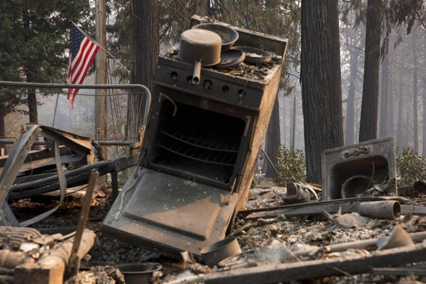 A US flag continues to fly in the backdrop of a burned out camper at a Magalia home after the Camp Fire burned through the region, fueled by high winds in Butte County, California, USA, 11 November 2018. EPA-EFE/FILE/PETER DASILVA
