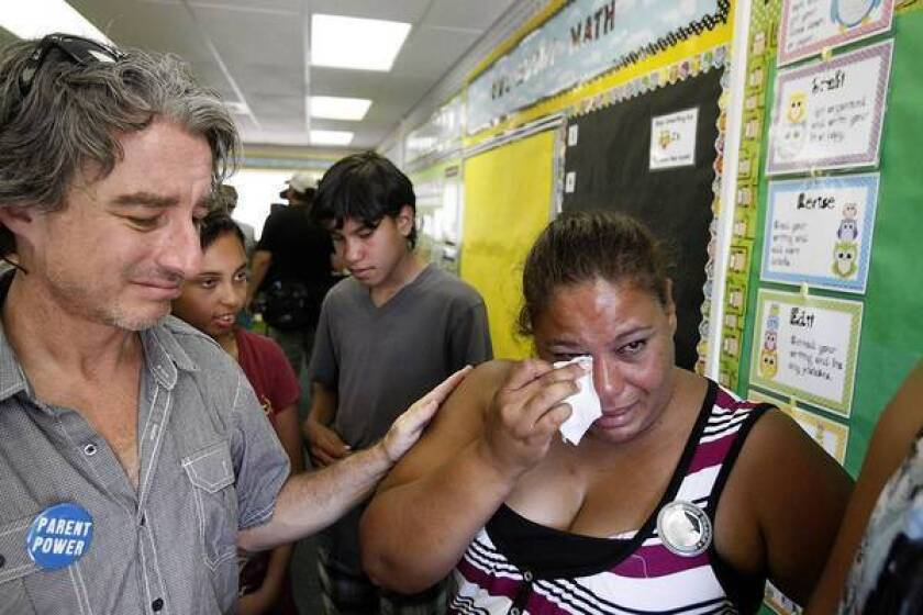 Doreen Diaz, right, a Parent Revolution organizer, sheds a tear as she visits a newly decorated classroom on Tuesday. With her is Ben Austin, executive director of Parent Revolution, the Los Angeles nonprofit that lobbied for the parent trigger law and trained Desert Trails parents on how to use it.
