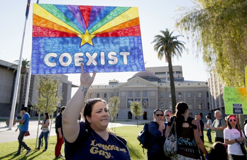 Jo Beaudry joins nearly 250 gay rights supporters protesting SB 1062 Friday in Phoenix. The protesters demanded Gov. Jan Brewer veto legislation that would allow business owners to refuse to serve gays by citing their religious beliefs.