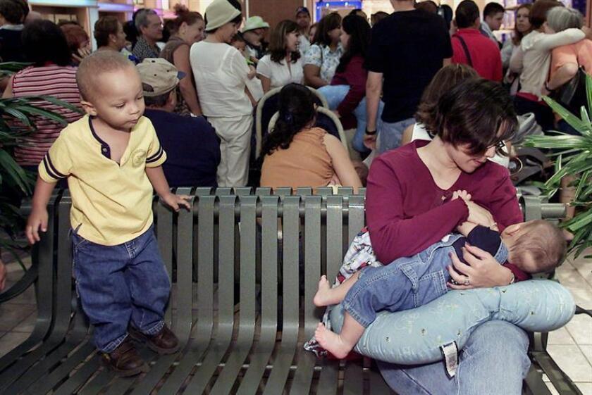 Un niño curioso observa mientras una madre lacta a su bebe. EFE/Archivo