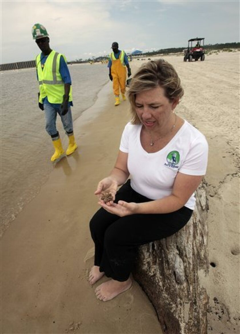 Clean up workers hired by BP walk along the beach as Casi Callaway, Executive Director and Baykeeper of Mobile Baykeeper holds clumps of sandy oil that washed up on Dauphin Island, Ala., Thursday, June 3, 2010. Oil from the Deepwater Horizon disaster has started washing ashore on the Alabama coast. (AP Photo/Dave Martin)