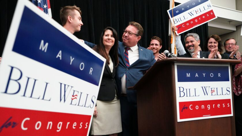 Standing with his wife, Bettie and sons, Matt (right) and Eli (left), El Cajon Mayor Bill Wells on Tuesday at a press conference announced his candidacy for the 50th Congregational District.