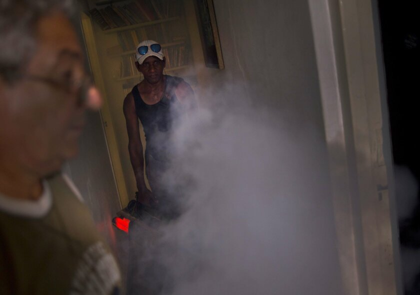 In this Aug. 26, 2016 photo, a government fumigator sprays a home for mosquitos in Havana, Cuba, Friday, August 26, 2016. Six months after President Raul Castro declared war on the Zika virus in Cuba, a militarized nationwide campaign of intensive mosquito spraying, monitoring and quarantine appear