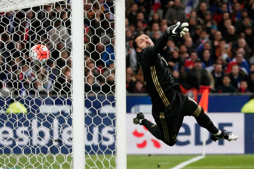 In this photo taken on Tuesday, March 29, 2016, Russia goalkeeper Igor Akinfeev dives for the ball in an attempt to stop a goal by France's Dimitri Payet during the international friendly soccer match between France and Russia in Saint Denis, north of Paris, France. (AP Photo/Thibault Camus)