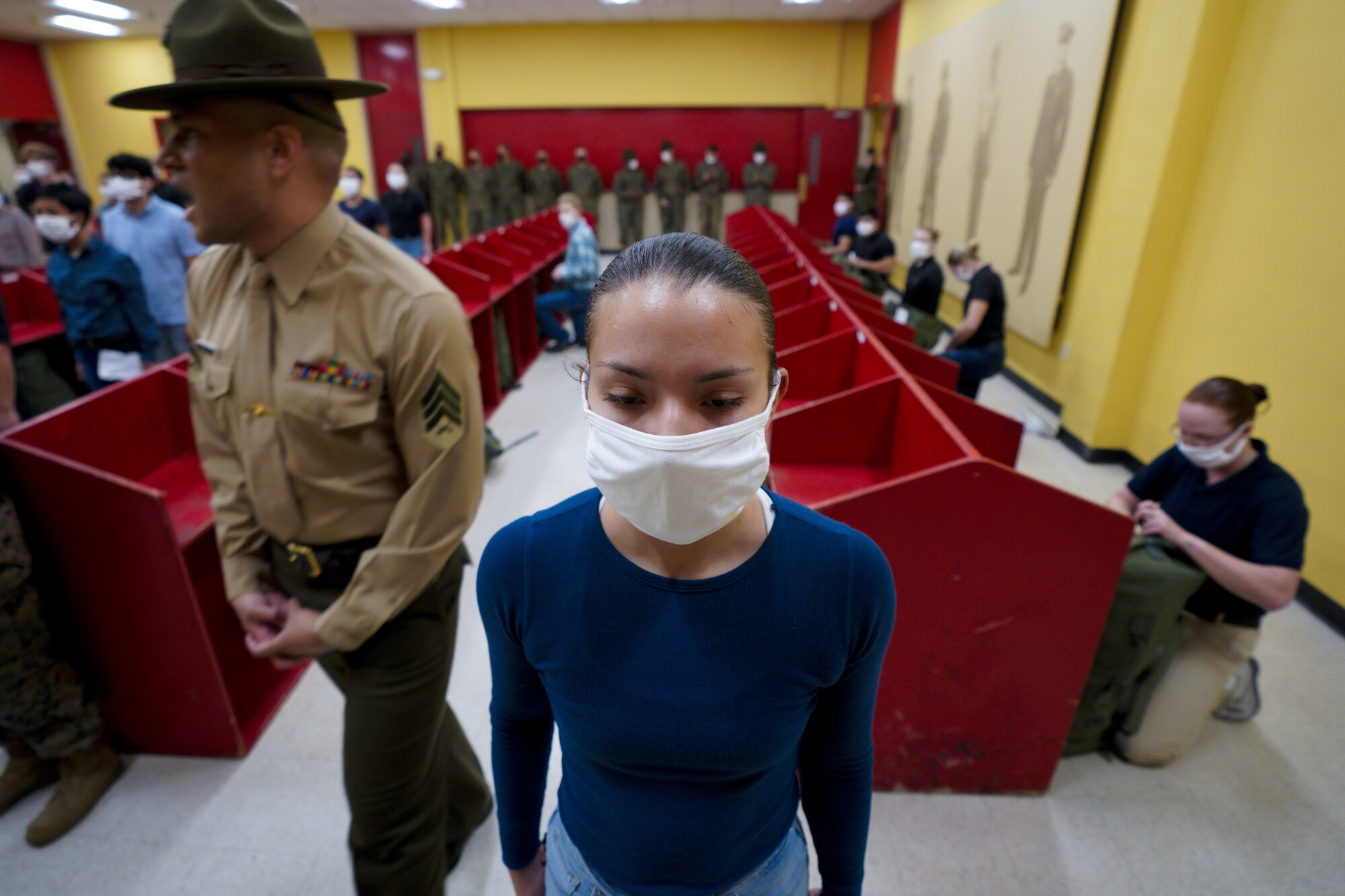A female Marine recruit stands at attention