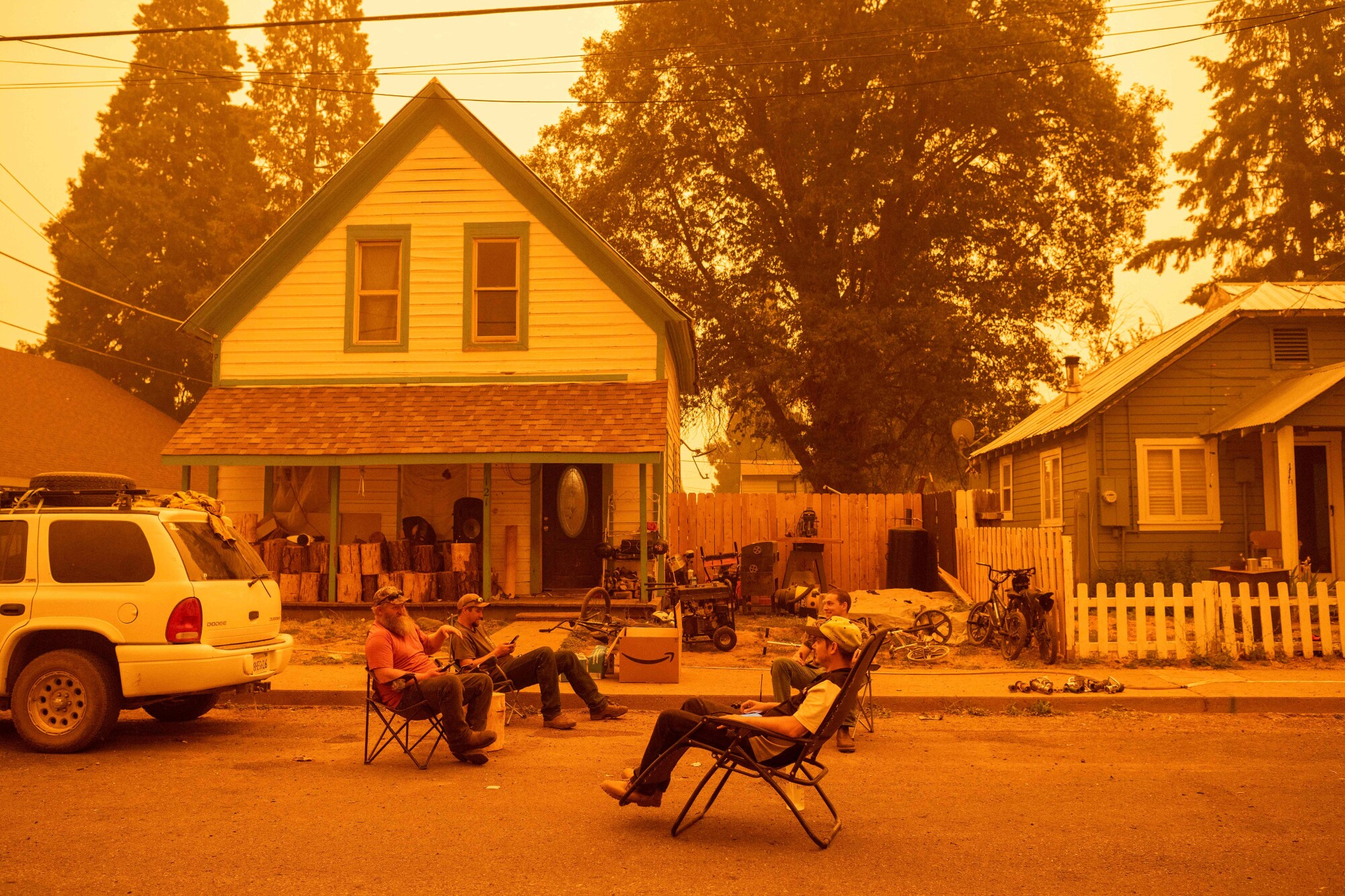 Residents sit in chairs in the street beneath an orange sky.