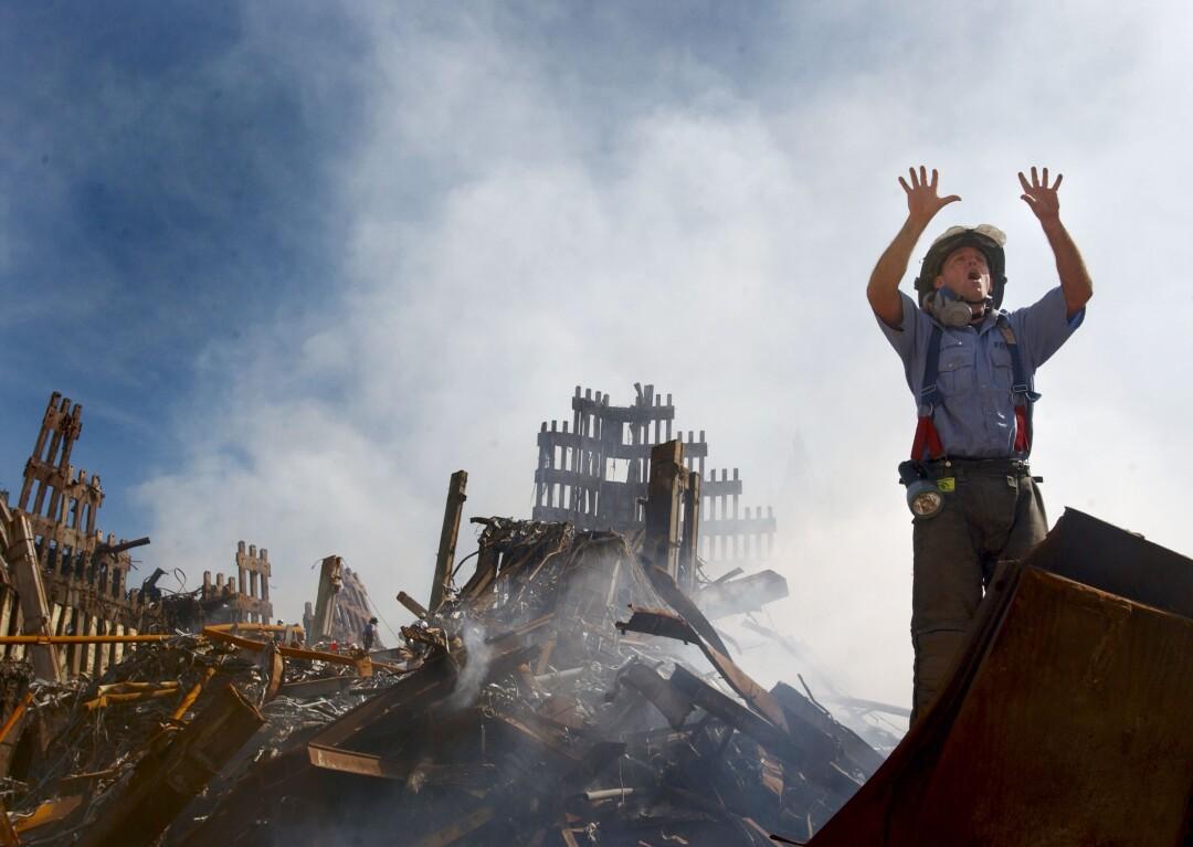 یک آتش نشان 10 انگشت بلند می کند و جلوی آوارهای سوزان ایستاده است