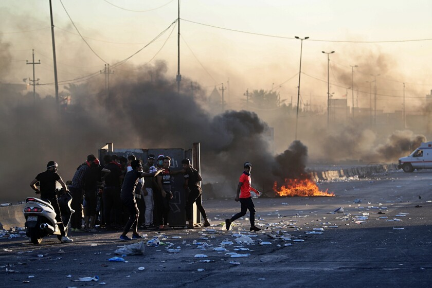 Anti-government protesters set fires, closing down a street, during a demonstration in Baghdad on Oct. 4.