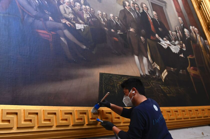 A preservationist uses a brush to clean the gold frame around a painting inside the US Capitol Rotunda.