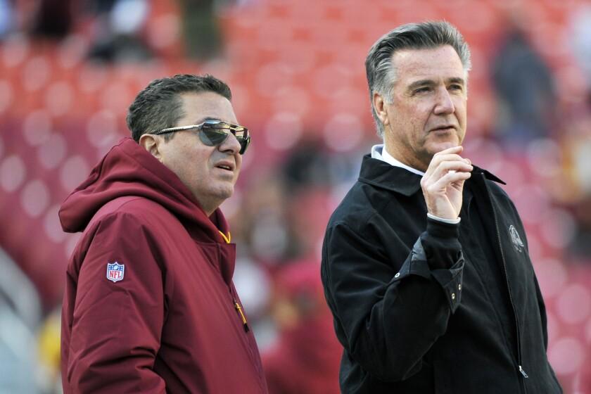 Washington Redskins owner Dan Snyder and team president Bruce Allen talk on the field prior to a 2018 NFL game