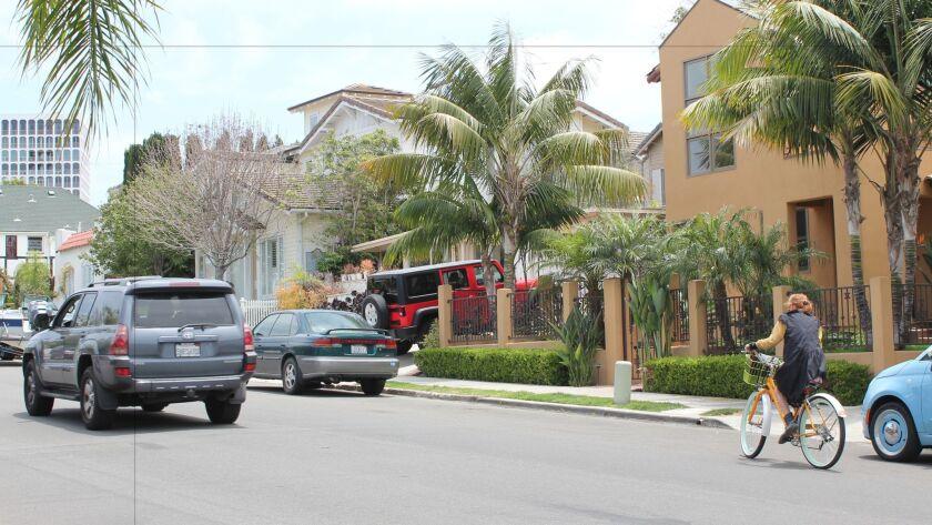 A car passes a bicyclist riding on a non-designated road in La Jolla.