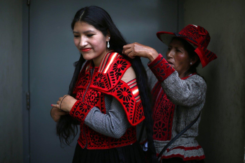 """En esta imagen, la bailarina indígena andina Waira Sacsi recibe ayuda con su peinado de su madre Flor antes del comienzo de la lucha ritual """"Takanakuy"""" a las afueras de Lima, Perú, el día de Navidad. Los bailarines abren el acto con la música tradicional andina conocida como """"Huaylia"""". (AP Foto/Martin Mejia)"""