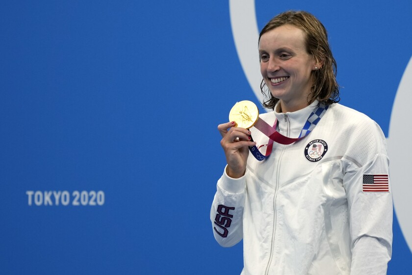 Katie Ledecky of the United States poses with her gold medal after winning the women's 1500-meters freestyle final at the 2020 Summer Olympics, Wednesday, July 28, 2021, in Tokyo, Japan. (AP Photo/Martin Meissner)