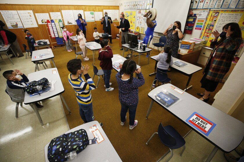 Kindergarteners sing and dance in a classroom