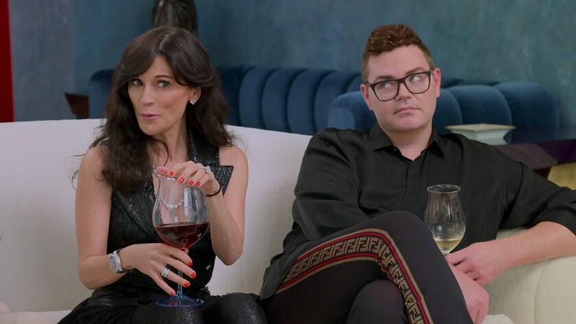 Two people sitting on a sofa holding large glasses of wine.