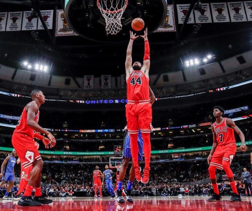 El defensa Nikola Mirotic (c), de los Bulls de Chicago Bulls, ante la mirada de sus compañeros Kris Dunn (i) y Justin Holiday (d), fue registrado este miércoles al atacar el aro que defendían los Magic de Orlando, durante un partido de la NBA, en el United Center de Chicago (Illinois, EE.UU.). EFE