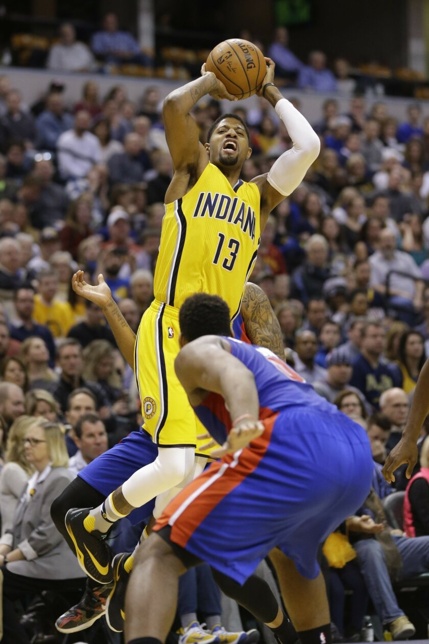 Indiana Pacers forward Paul George (13) is fouled as he shoots over Detroit Pistons center Andre Drummond, front, during the second half of an NBA basketball game in Indianapolis, Saturday, Feb. 6, 2016. The Pacers defeated the Pistons 112-104. (AP Photo/Michael Conroy)